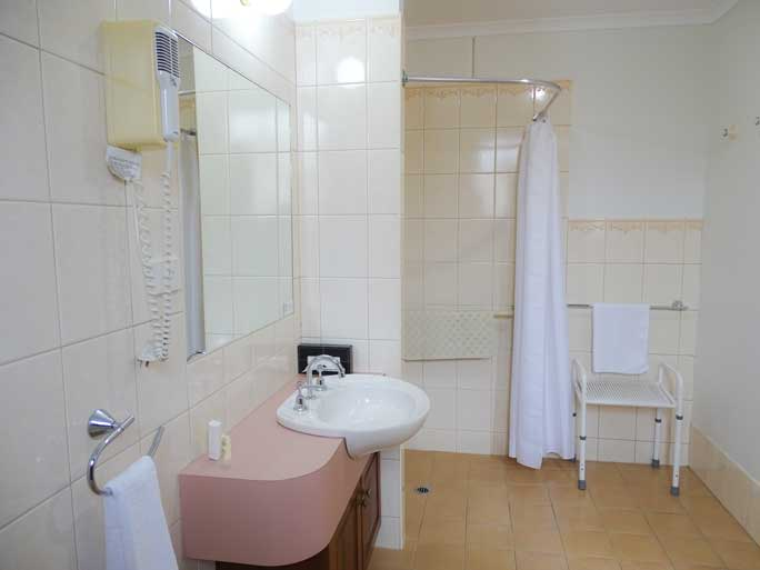 Bathroom of Deluxe Queen room with disability access accommodates 1 - 2 people